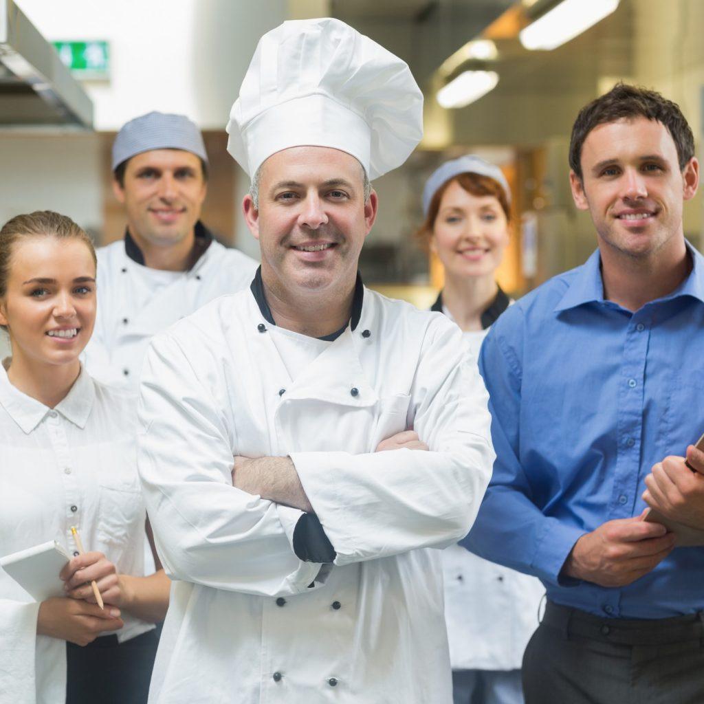 Chef de cuisine avec son équipe derrière lui dans une cuisine professionel.