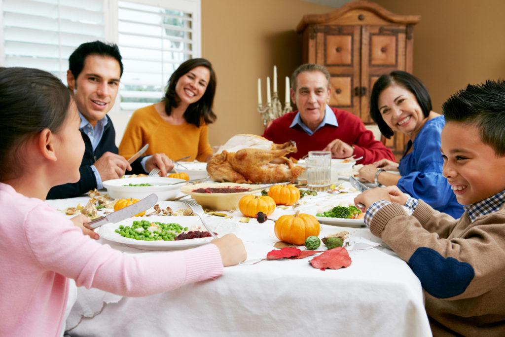 Famille souriante à la table.