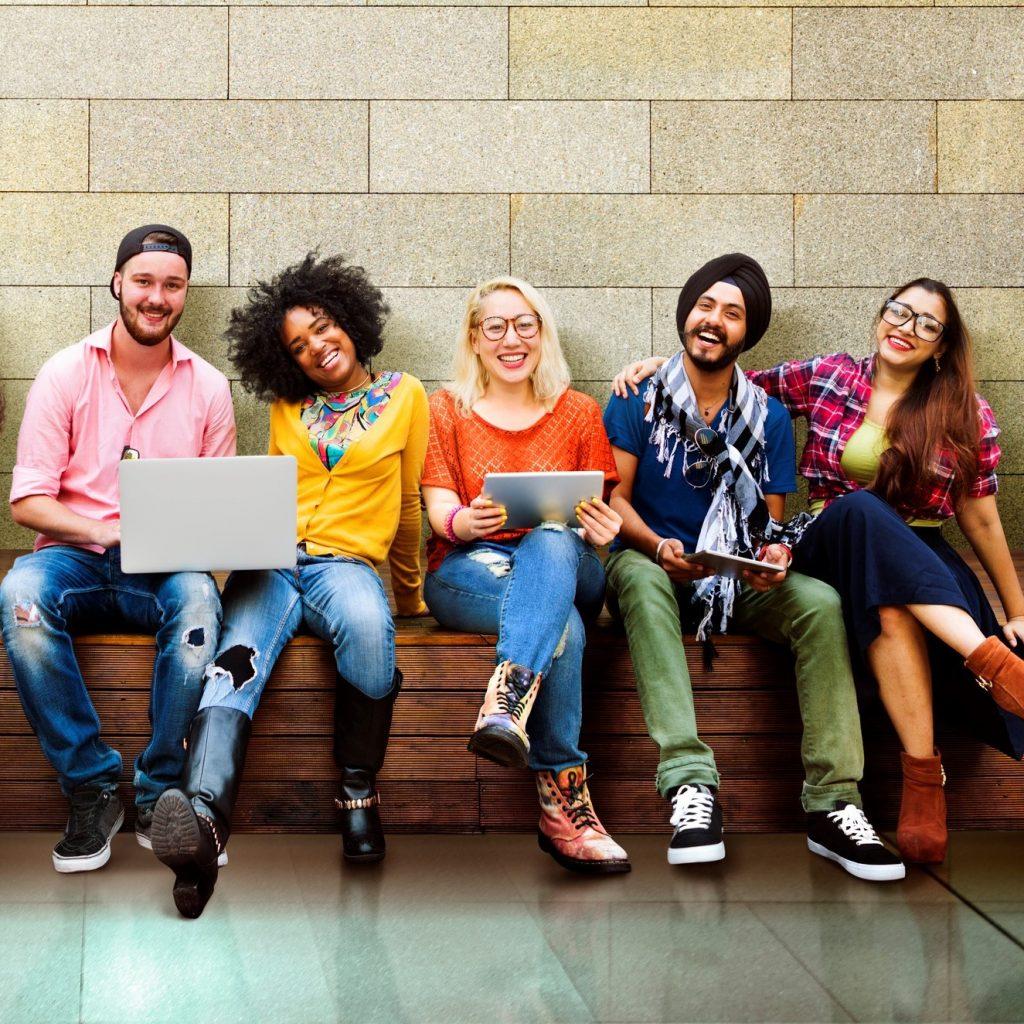 Groupe de jeunes adultes assis sur un banc avec des ordinateurs portables et des tablettes dans les mains.