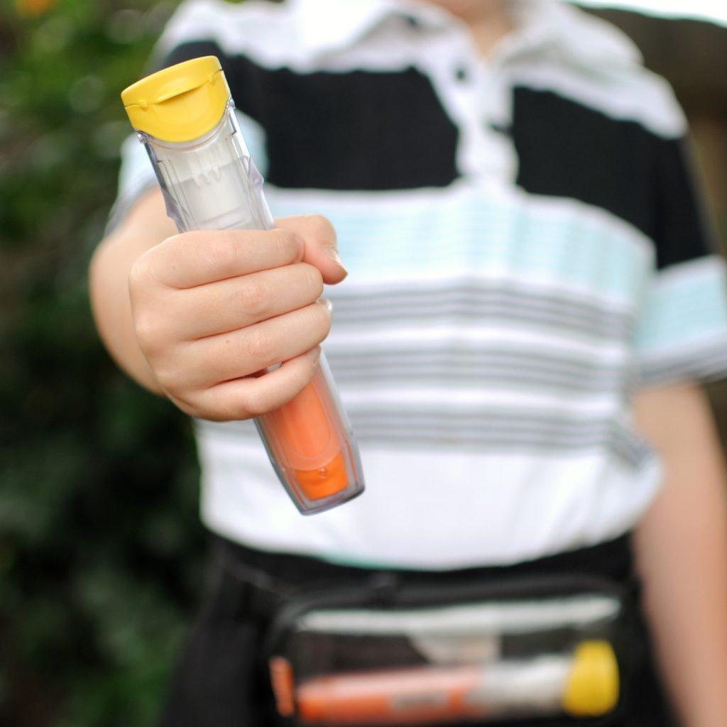 Enfant avec un auto-injecteur d'épinéphrine dans la main et un étui à la taille qui contient un deuxième auto-injecteur.