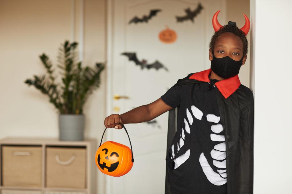 Garçon portant un couvre-visage déguisé en costume d'Halloween