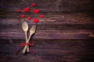 Table de bois avec une cuillère, une fourchette et des coeurs