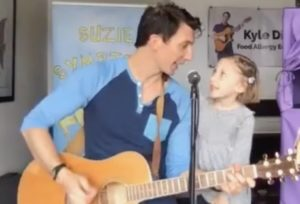 Kyle Dine performing with his daughter Zora