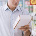 Homme à l'épicerie lisant des ingrédients sur une boîte