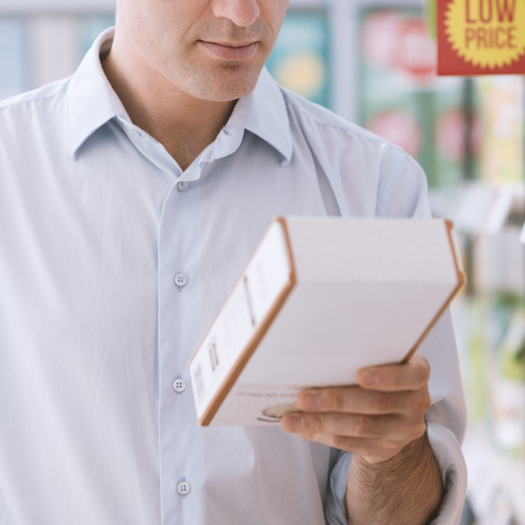 Man doing grocery shopping at the supermarket and reading a food label on a box, shopping and nutrition concept